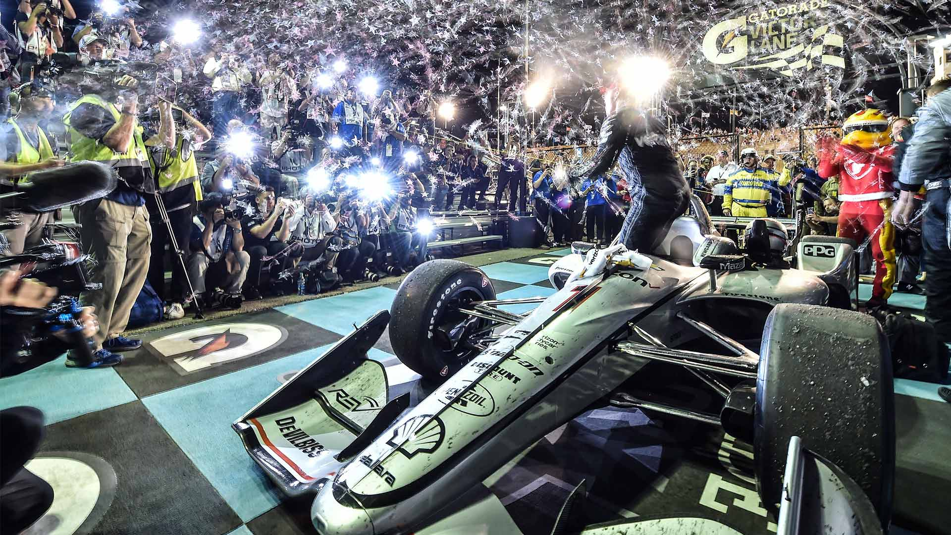 Cameras flashing and confetti flying as Josef Newgarden exits his car in victory circle